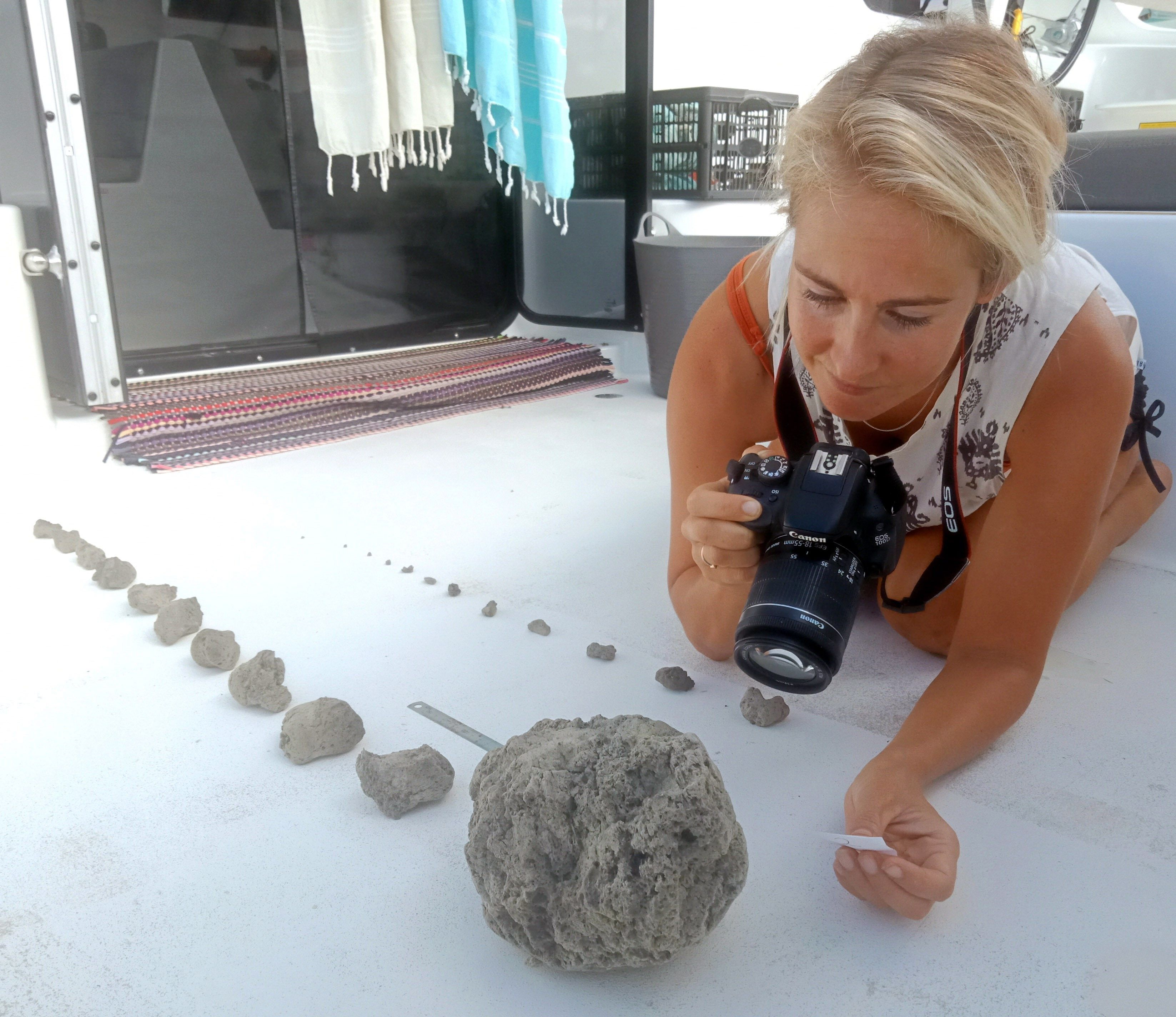 Una tripulante del catamarán Roam fotografía algunos de los fragmentos de piedra pómez rescatados del mar.   Foto: EFE