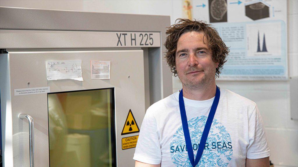 Richard Johnston, líder de la investigación, tiene a su espalda el escáner encargado de hacer la microtomografía de rayos X. / Johnston et al.