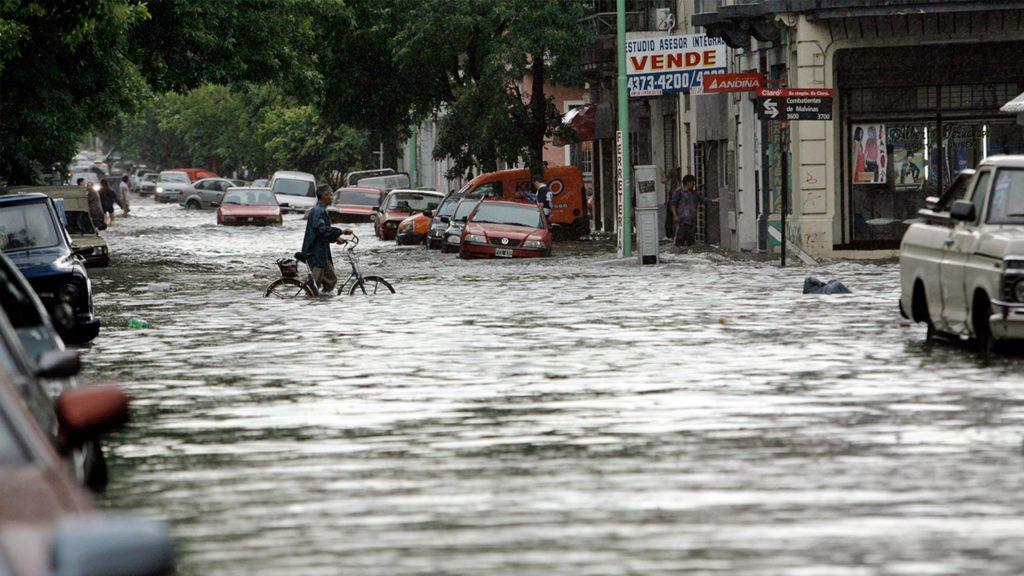 Un hombre camina con su bicicleta en medio de una inundación por una fuerte tormenta sobre Buenos Aires en 2009 | Foto: EFE / Leo La Valle