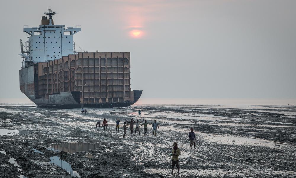 Trabajadores junto a un gran barco que está siendo desguazado en la playa de Chitagong, en Bangladesh. | FOTO: Katiekk