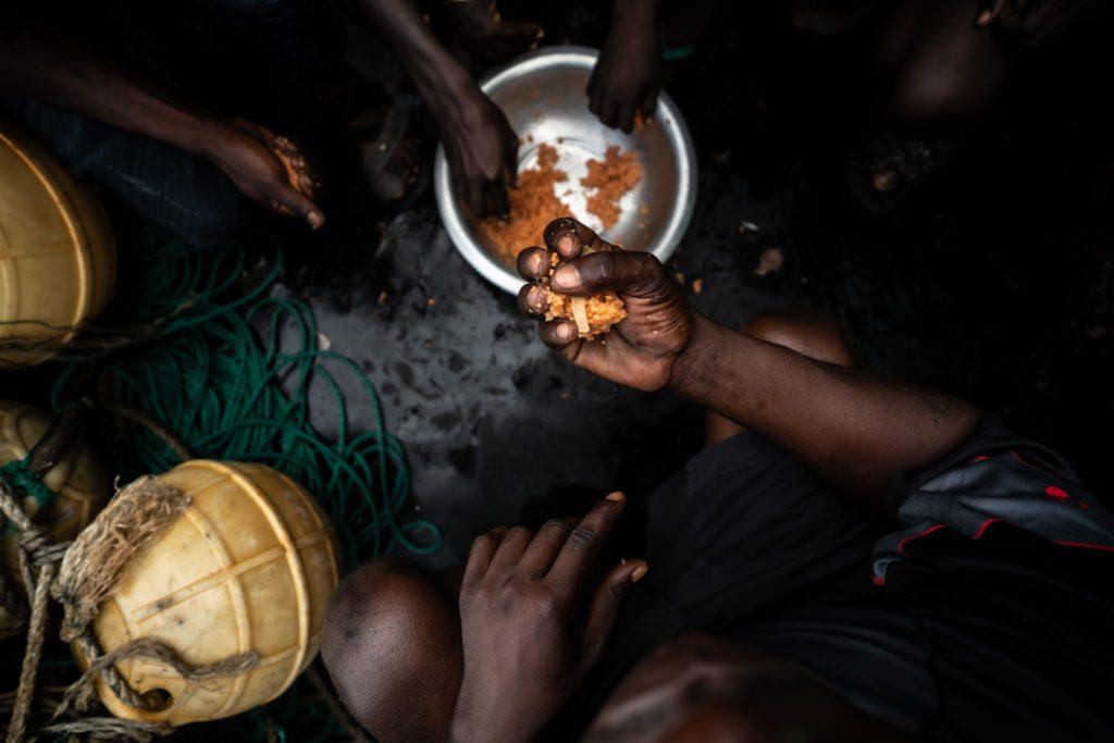 Trabajadores gambianos cogiendo puñados de harina de pescado. | FOTO: The Outlaw Ocean Project Fábio Nascimento