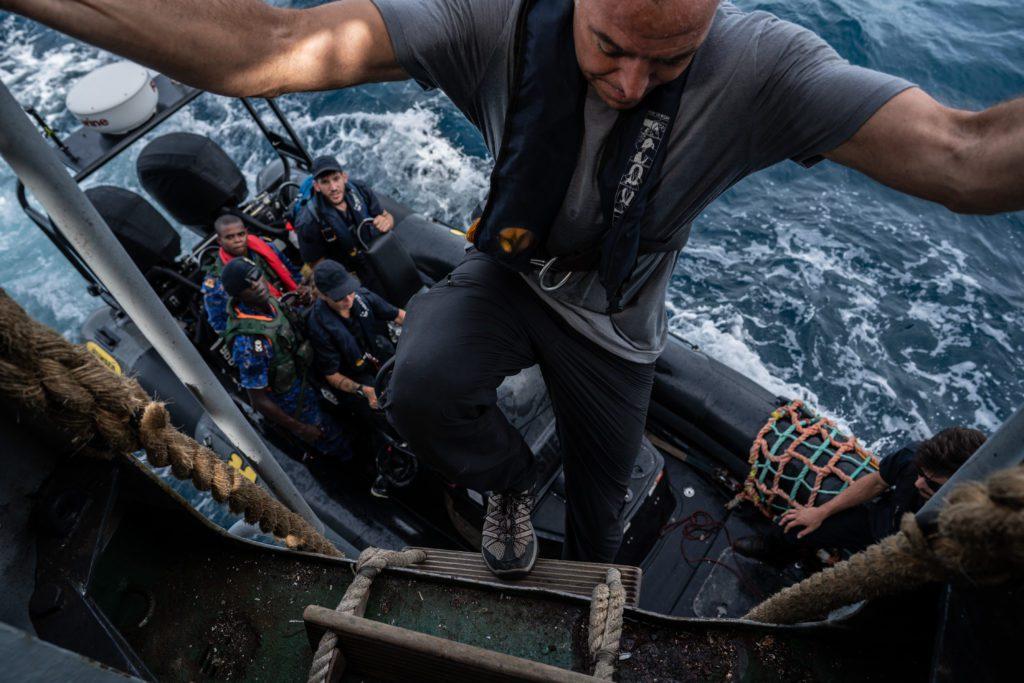 El reportero Ian Urbina monta en la lancha motora de Sea Shepherd junto a oficiales de la Marina de Gambia e inspectores de pesca del país africano. | FOTO: The Outlaw Ocean Project Fábio Nascimento